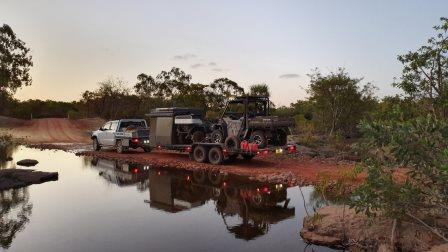 a ute with a large trailer carrying camper and smaller off road vehicle driving beside a creek